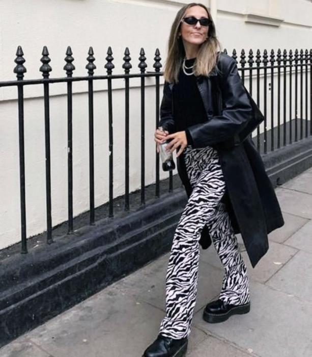 chica rubia con lentes de sol, top negro, abrigo negro de cuero, pantalones de estampado de zebra, botas negras de cuero