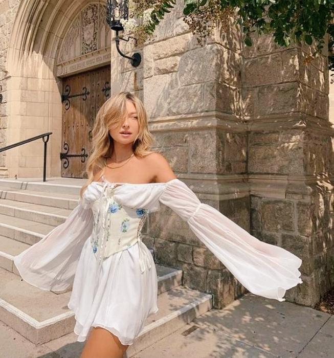 chica rubia usando un vestido blanco de mangas holgadas. corset blanco con flores azules estilo milkmaid