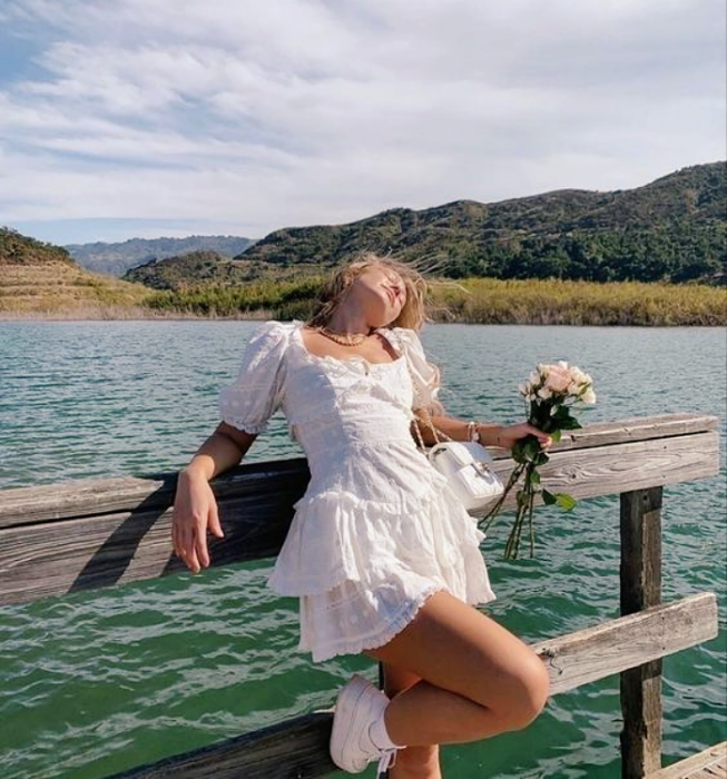 blonde girl wearing short sleeve white dress with voluminous skirt with trainers and flowers