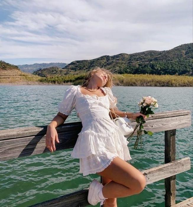 chica rubia usando un vestido blanco de manga corta con falda voluminosa con tenis deportivos y flores