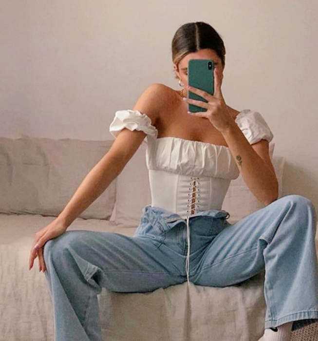 light haired girl wearing off shoulder milkmaid style white top and flared skinny jeans