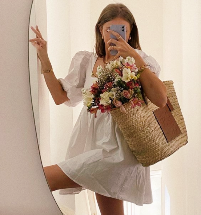 brown haired girl wearing white milkmaid style dress with flowers, beige knitted handbag