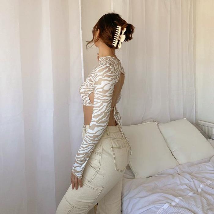 chica de cabello castaño con top blanco de cebra beige con pantalones beige a la cintura