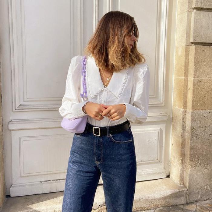 chica de cabello claro usando una blusa blanca con cuello bobo, jeans a la cintura
