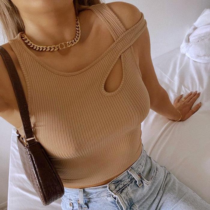 top beige claro de tirantes cruzados, jeans a la cintura claros y bolso pequeño de cuero café