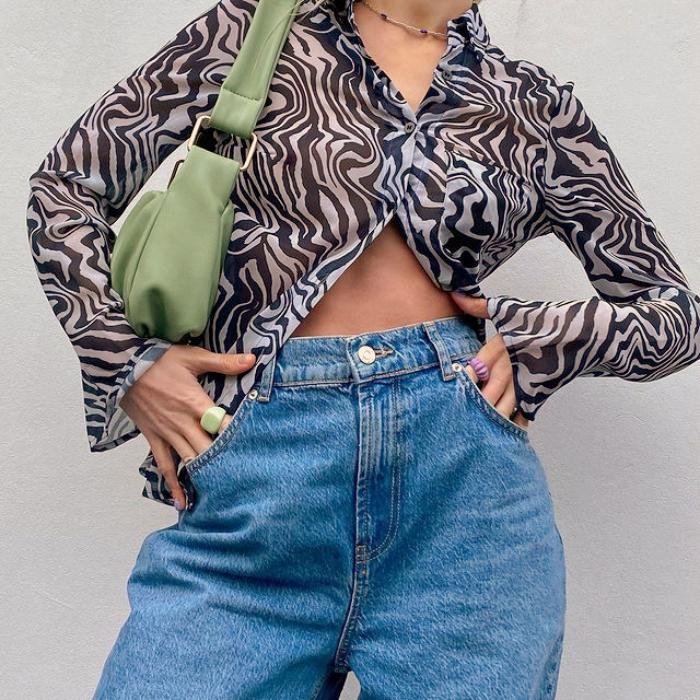 blusa semitransparente de cebra con botones al frente y manga larga, jeans a la cintura y bolso pequeño de cuero verde claro