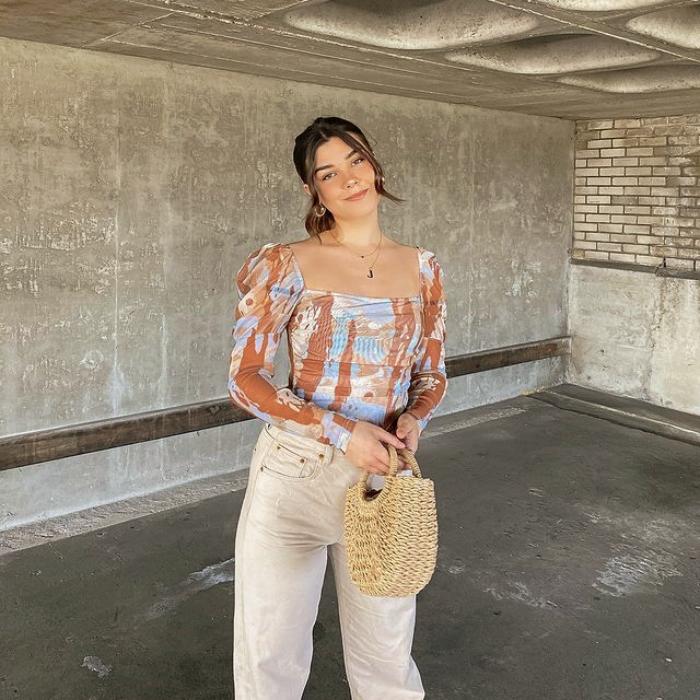 chica de cabello castaño usando un top celeste con líneas naranjas, pantalones beige a la cintura y bolso de mano pequeño beige