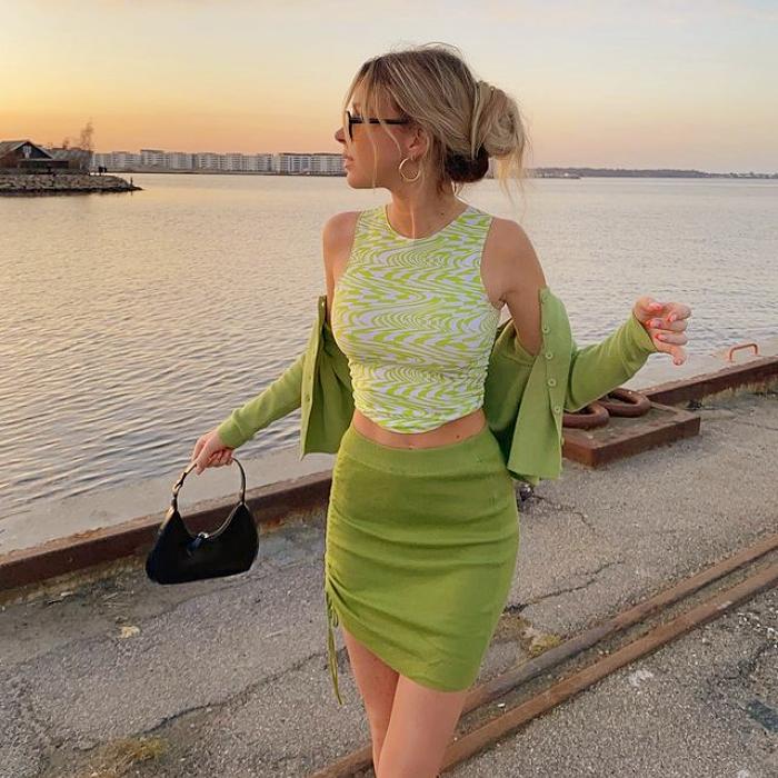 chica rubia con top verde claro, cárdigan verde y minifalda verde, bolso pequeño de cuero verde oscuro