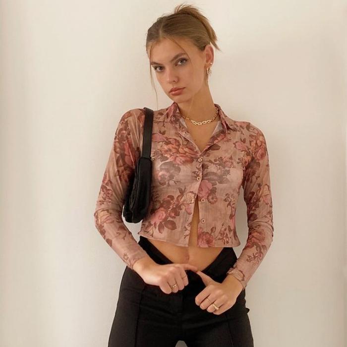 chica rubia usando un top semitransparante rosa con estampado floral, manga larga, jeans negros a la cintura y bolso negro de cuero