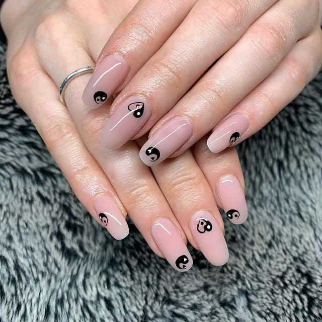 Chica mostrando sus uñas con diseño Yin Yang en color blanco con nude
