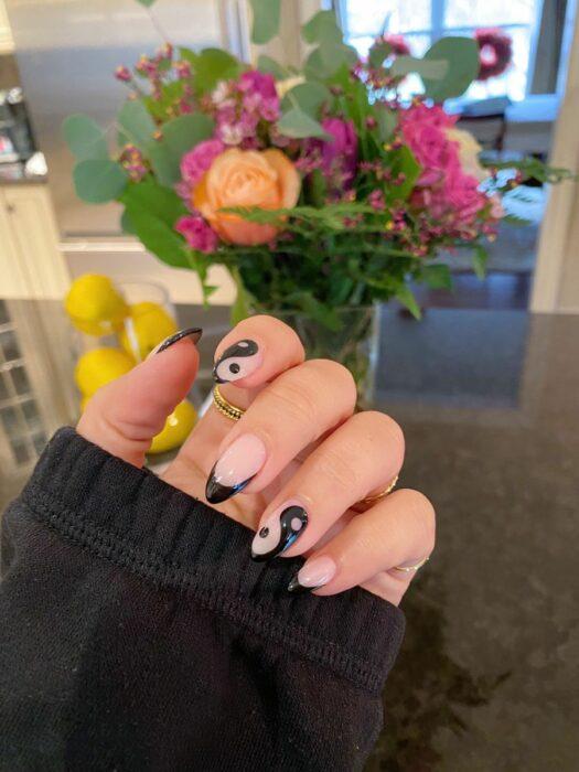 Chica mostrando sus uñas con diseño Yin Yang en color nude con negro