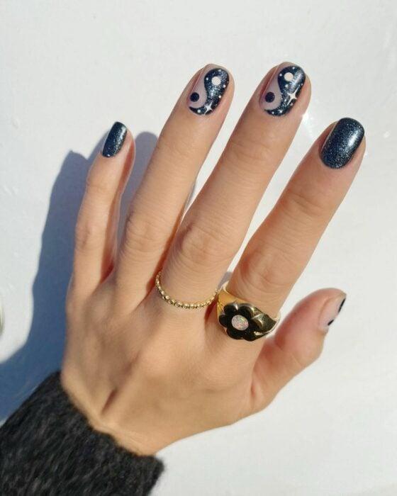 Chica mostrando sus uñas con diseño Yin Yang en color gris con azul