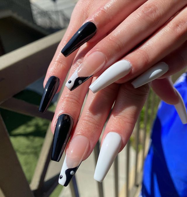 Chica mostrando sus uñas con diseño Yin Yang en color blanco con negro