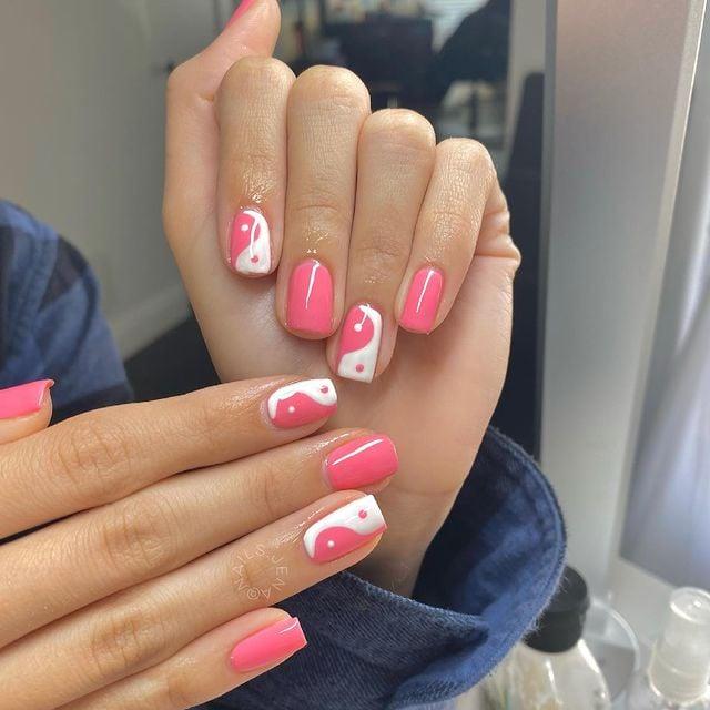 Chica mostrando sus uñas con diseño Yin Yang en color blanco con rosa