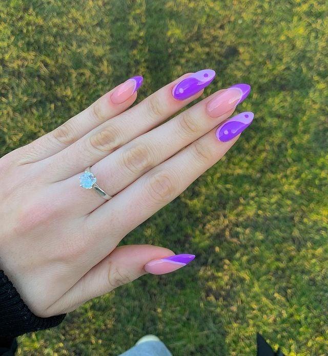 Chica mostrando sus uñas con diseño Yin Yang en color morado con rosa