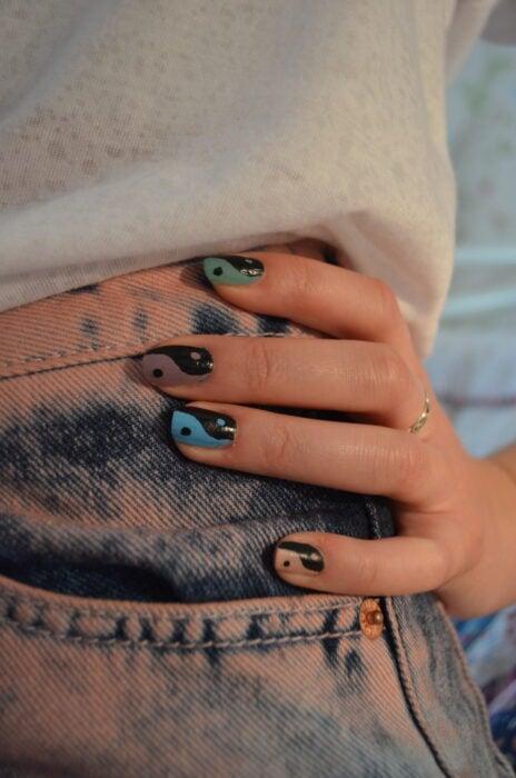 Chica mostrando sus uñas con diseño Yin Yang en color azul y café