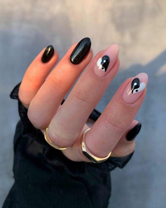 Chica mostrando sus uñas con diseño Yin Yang en color negro con blanco y corazones