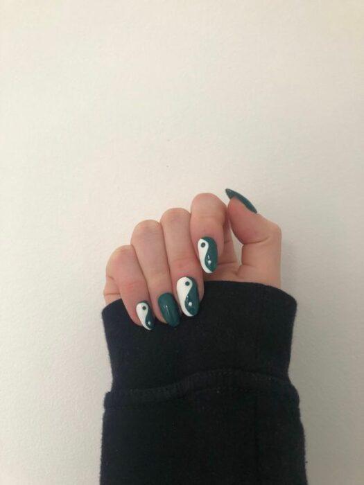 Chica mostrando sus uñas con diseño Yin Yang en color verde con blanco