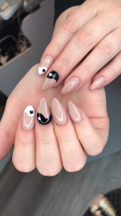 Chica mostrando sus uñas con diseño Yin Yang en color blanco, nude y negro