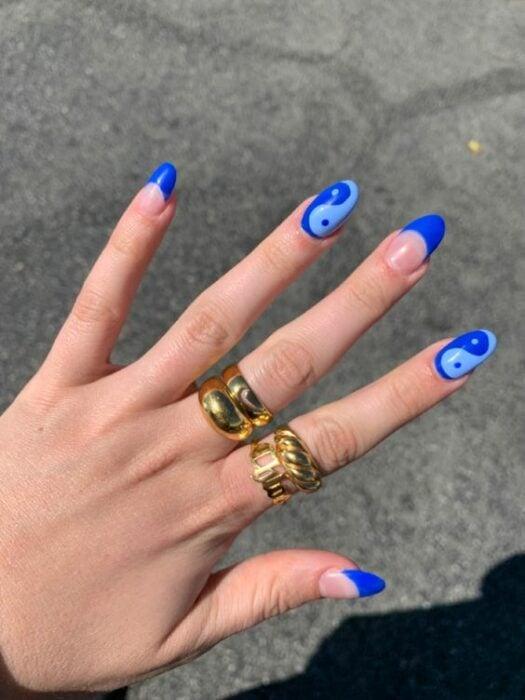 Chica mostrando sus uñas con diseño Yin Yang en colores azules