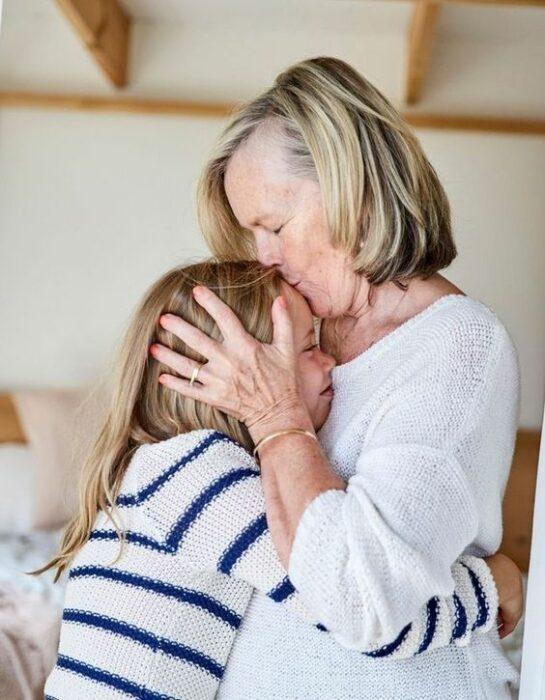 Abuela dando un beso a su nieta en la frente