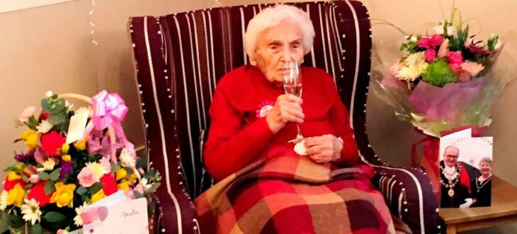 Abuelita bebiendo una copa de vino tinto para celebrar su cumpleaños 105