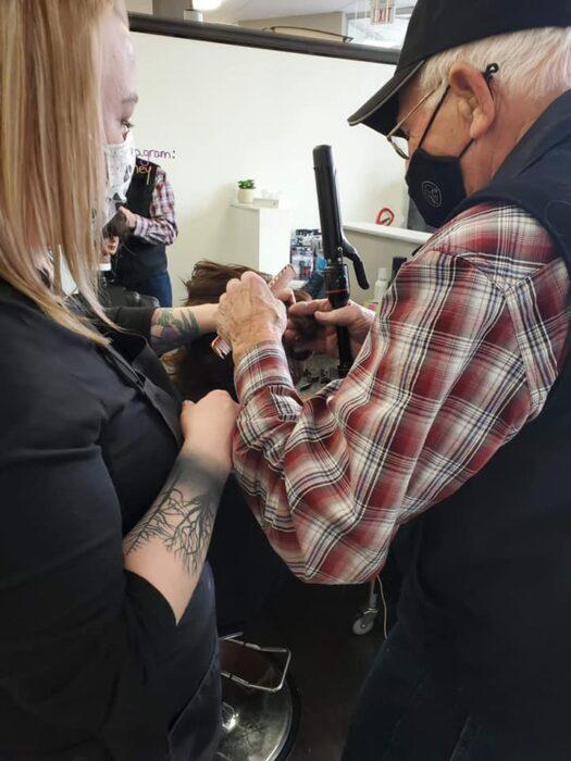 Abuelito sujetando una pinza para rizos mientras practica con una muñeca de peinados