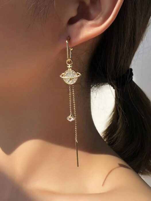 Chica usando unos aretes en forma de planeta con diamantes