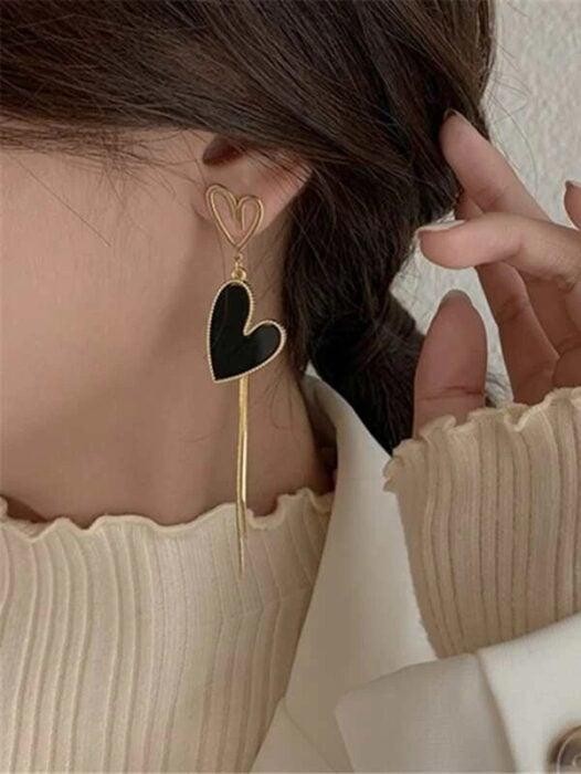 Chica usando unos aretes largos de color negro con dorado en forma de corazón
