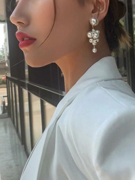 Chica usando unos aretes en forma de perlas