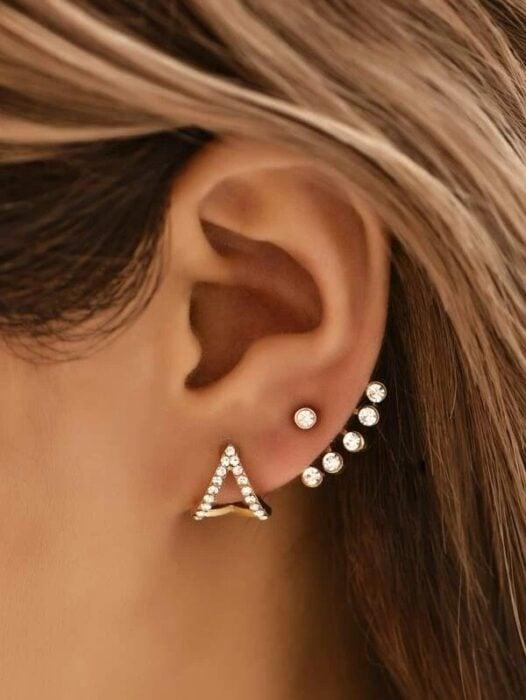 Chica usando unos aretes en forma de triangulo con algunos puntos