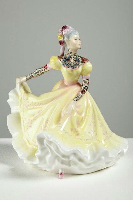 Muñeca de porcelana con vestido amarillo  teñida con tatuajes por Jessica Harrinson; Artista agrega tatuajes a muñecas de porcelana y se ven hermosas