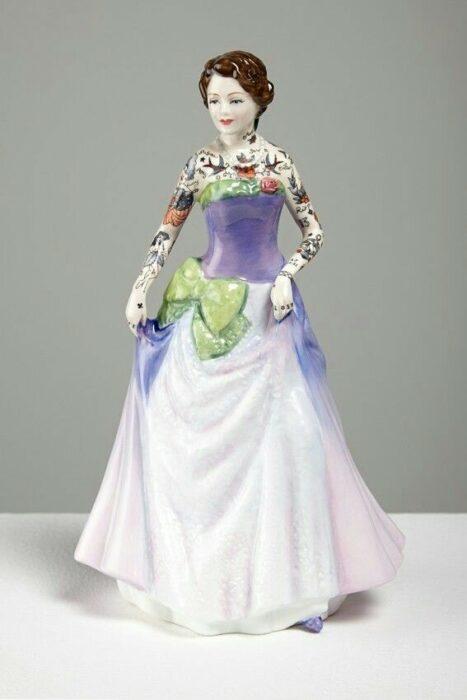 Muñeca de porcelana con vestido lila y moño verde teñida con tatuajes por Jessica Harrinson; Artista agrega tatuajes a muñecas de porcelana y se ven hermosas