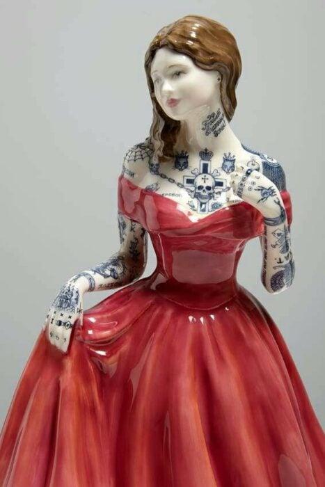 Muñeca de porcelana con vestido rojo cereza  teñida con tatuajes por Jessica Harrinson; Artista agrega tatuajes a muñecas de porcelana y se ven hermosas