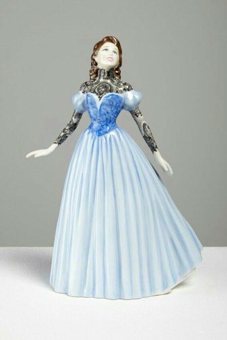 Muñeca de porcelana con vestido azul y blanco  teñida con tatuajes por Jessica Harrinson; Artista agrega tatuajes a muñecas de porcelana y se ven hermosas