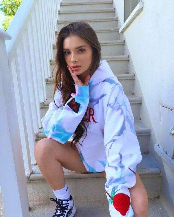 Chica usando una sudadera grande mientras está sentada en las escaleras tomándose una fotografía