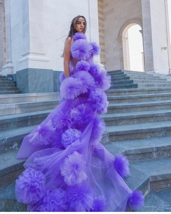 Girl wearing a purple dress with big pompoms