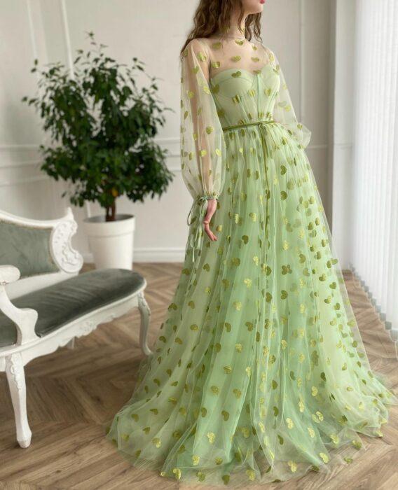 Chica usando un vestido de color verde con corazones en color dorado