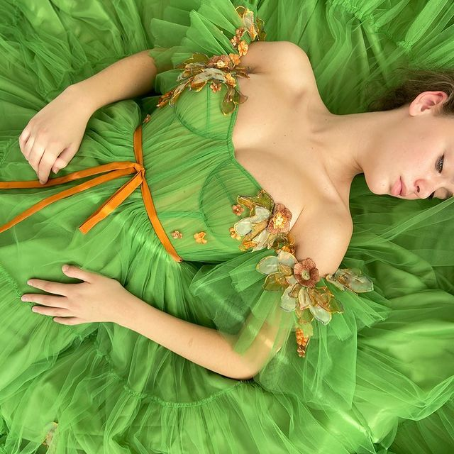 Girl wearing a green dress with orange details