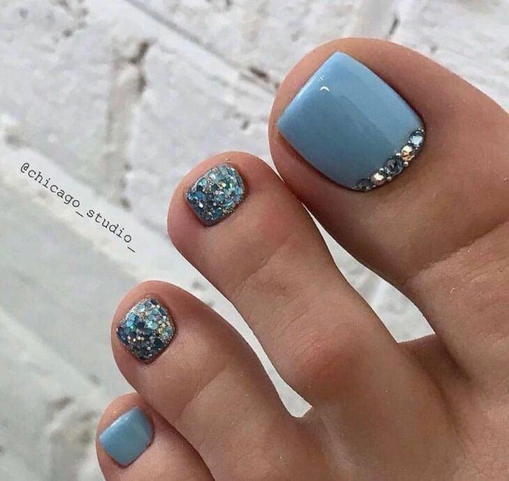 Diseño de uñas para pies en color azul con pedrería