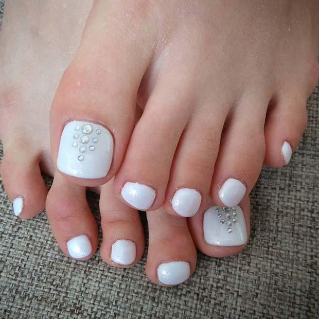 Diseño de uñas para pies en color blanco con pedrería