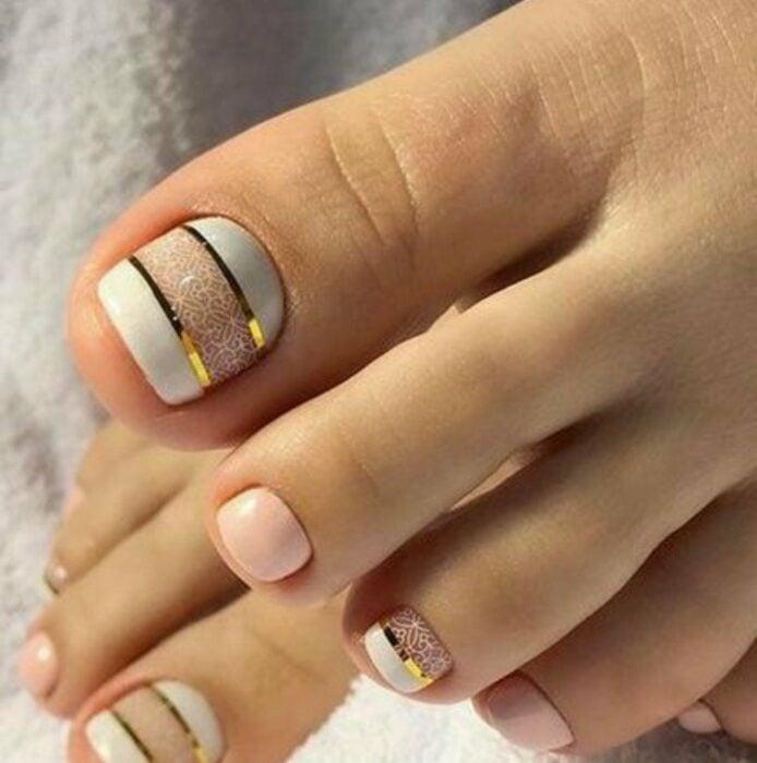 Diseño de uñas para pies en color  blanco con líneas doradas y blancas