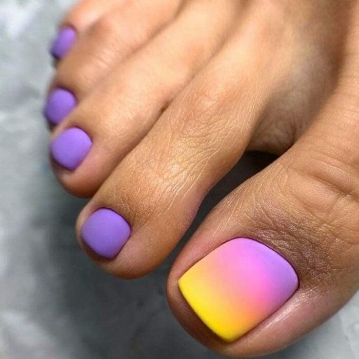 Diseño de uñas para pies en colores morado con amarillo y rosa