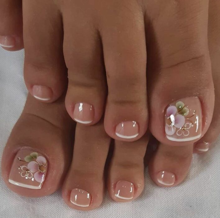 Diseño de uñas para pies en estilo french con flores