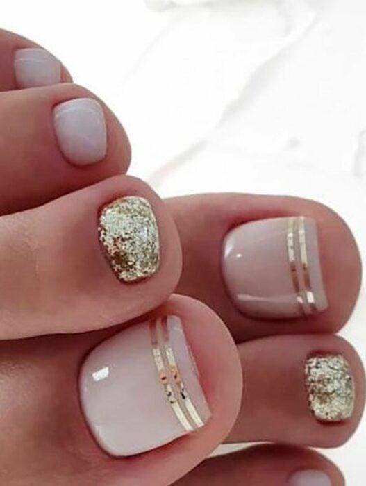 Diseño de uñas para pies en color nude con destellos en dorado