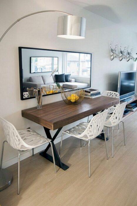 Mesa pegada a la pared y bajo un espejo con tres sillas