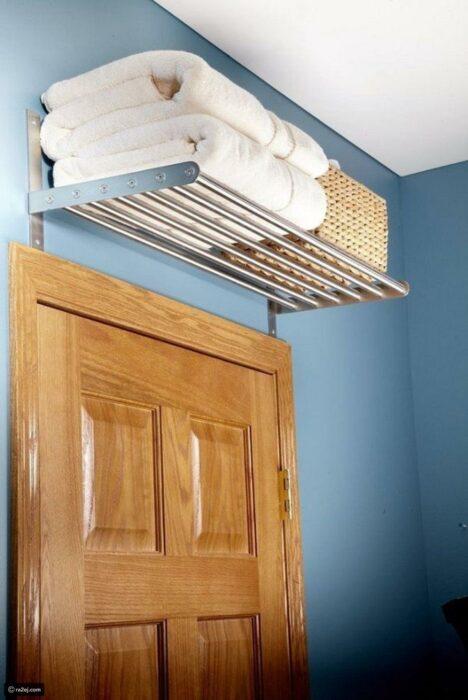 Mueble sobre la puerta del baño para colocar toallas y productos