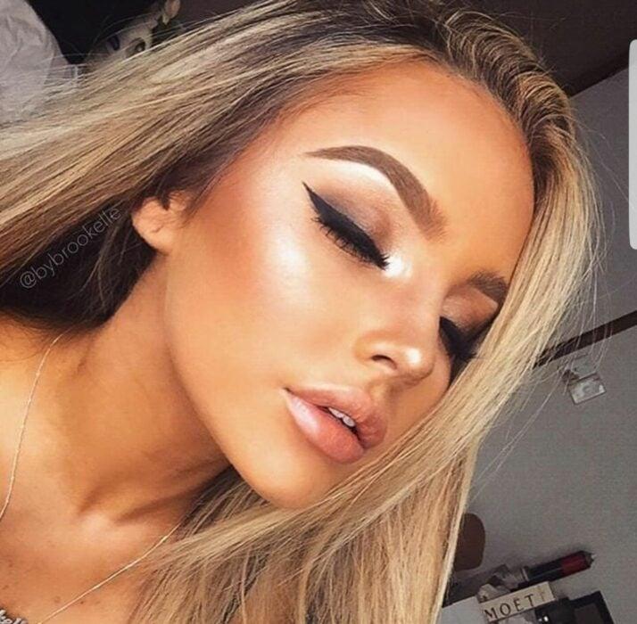 Chica usando iluminador en el rostro; Guía para usar iluminador como una maquillista profesional