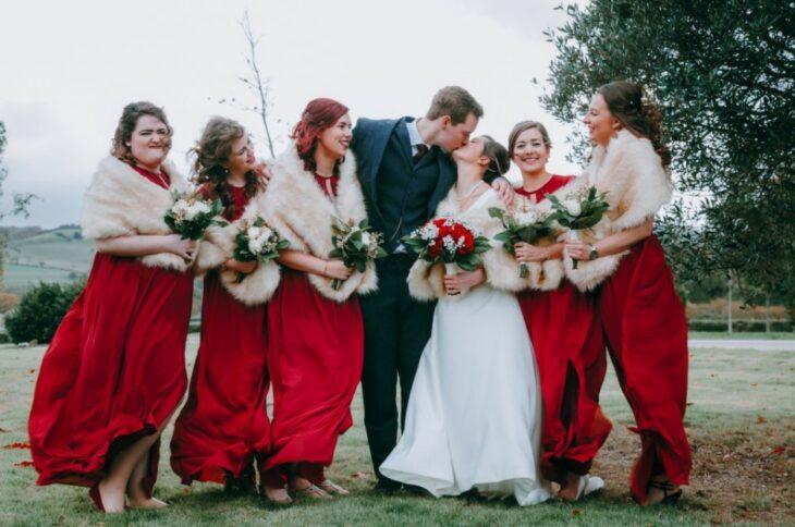 Damas de honor con abrigos durante la sesión de fotos de la boda junto a los novios