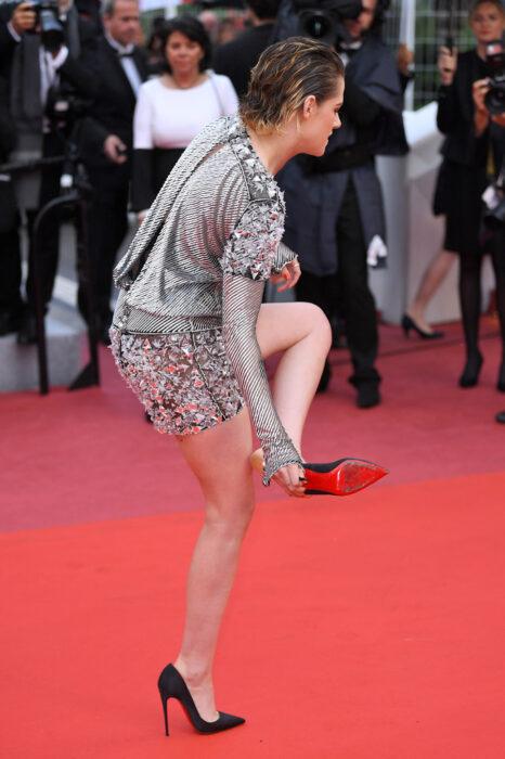 Kristen Stewart quitandose los zapatos mientras está en una alfombra roja
